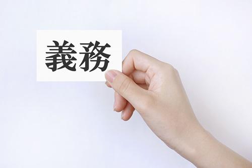 義務と書かれたカードを持つ手